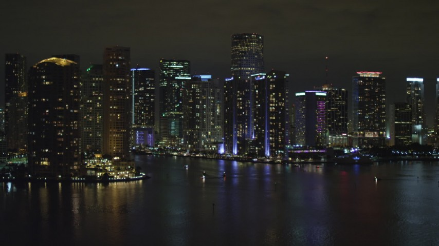 5K aerial \video tilt from the bay to reveal waterfront towers of the Downtown Miami at night, Florida Aerial Stock Footage | AX0023_153