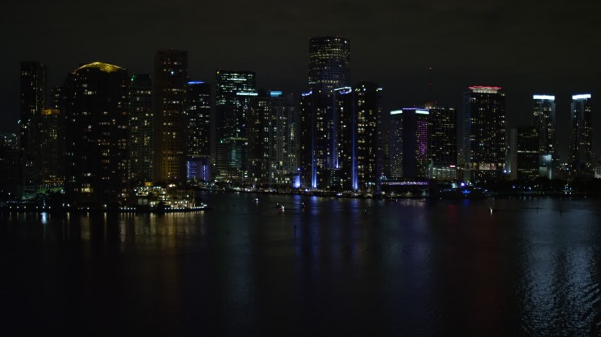 5K aerial \video tilt from the bay to reveal waterfront towers of the Downtown Miami at night, Florida Aerial Stock Footage   AX0023_153E