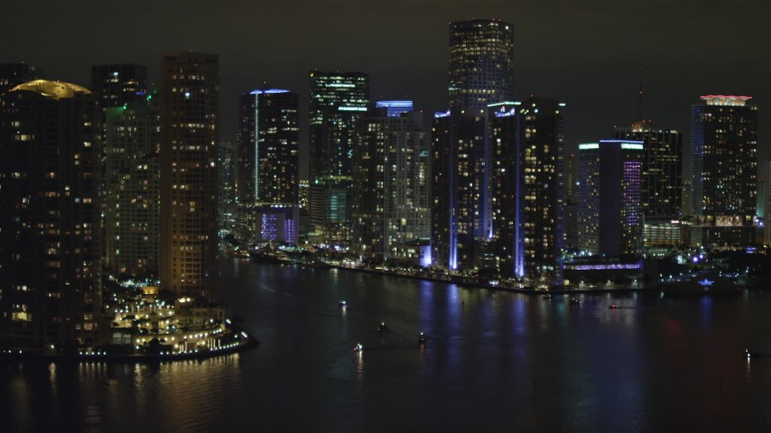5K stock footage aerial video approach tall high-rises by the Miami River at nighttime in Downtown Miami, Florida Aerial Stock Footage | AX0023_154