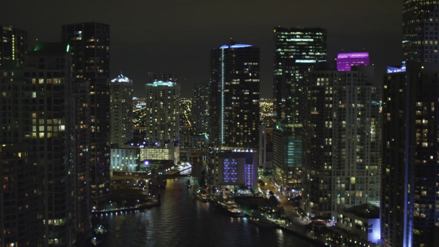 5K stock footage aerial video fly over Miami River past skyscrapers at night in Downtown Miami, Florida Aerial Stock Footage | AX0023_155