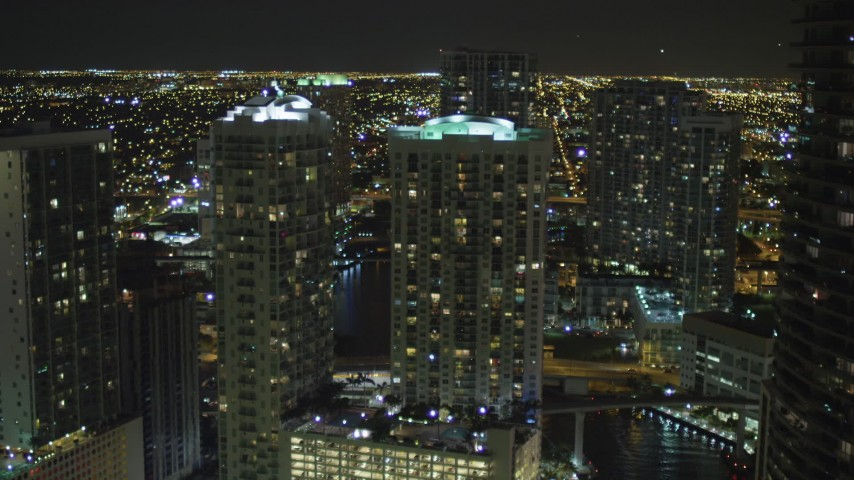 5K stock footage aerial video approach Brickell on the River from Miami River at night in Downtown Miami, Florida Aerial Stock Footage | AX0023_156