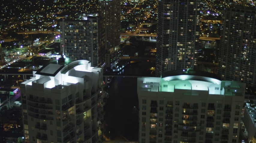 5K stock footage aerial video fly over Brickell on the River rooftops and tilt to Miami River at night in Downtown Miami, Florida Aerial Stock Footage | AX0023_157