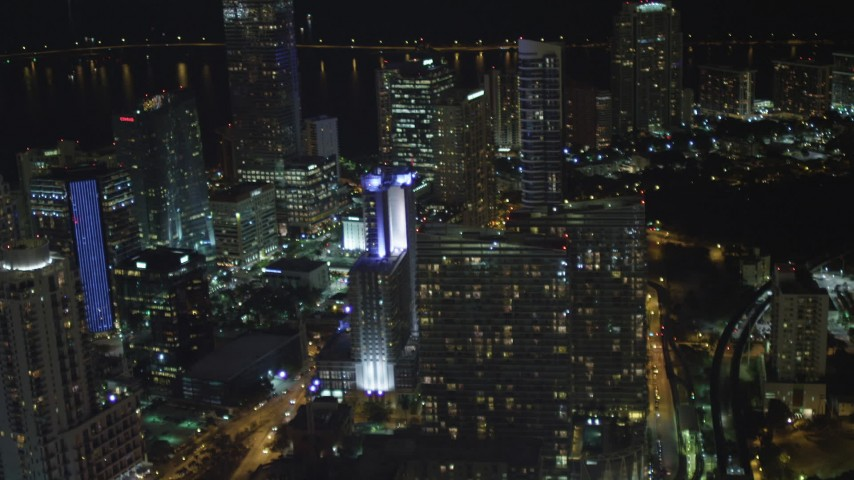 5K aerial video tilt from elevated rail and office building to reveal skyscrapers at night in Downtown Miami, Florida Aerial Stock Footage | AX0023_158