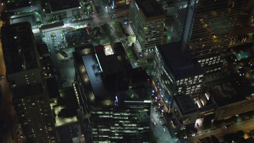 5K stock footage aerial video fly over tower and tilt to bird's eye of Brickell Avenue at night in Downtown Miami, Florida Aerial Stock Footage | AX0023_161