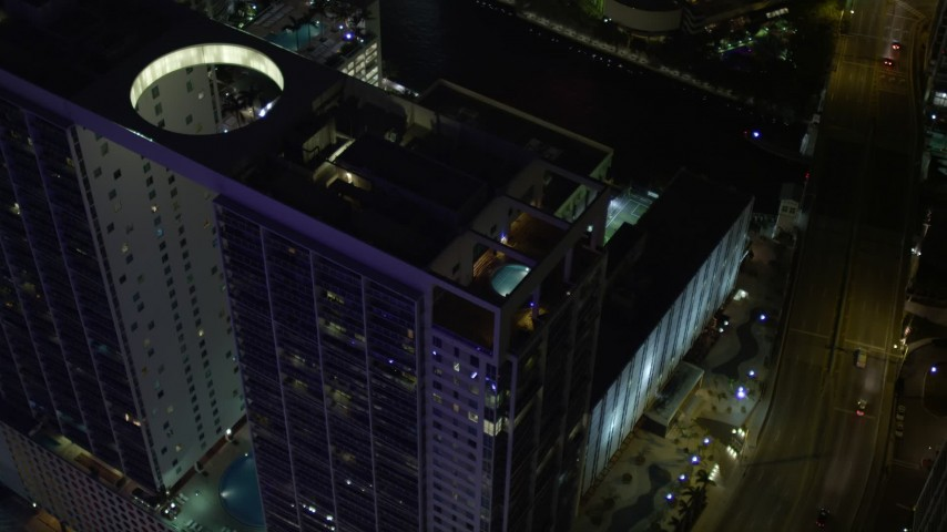 5K stock footage aerial video approach 500 Brickell and tilt to rooftop pool at night in Downtown Miami, Florida Aerial Stock Footage | AX0023_168