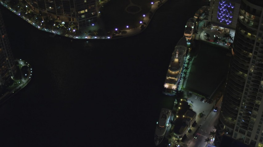 5K stock footage aerial video bird's eye orbit of a yacht docked on the river at night in Downtown Miami, Florida Aerial Stock Footage | AX0023_171