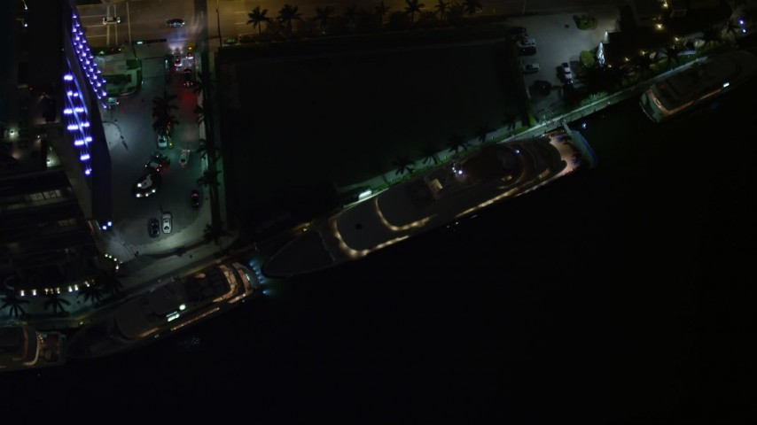 5K stock footage aerial video bird's eye orbit of a yacht on the Miami River at night in Downtown Miami, Florida Aerial Stock Footage | AX0023_173E