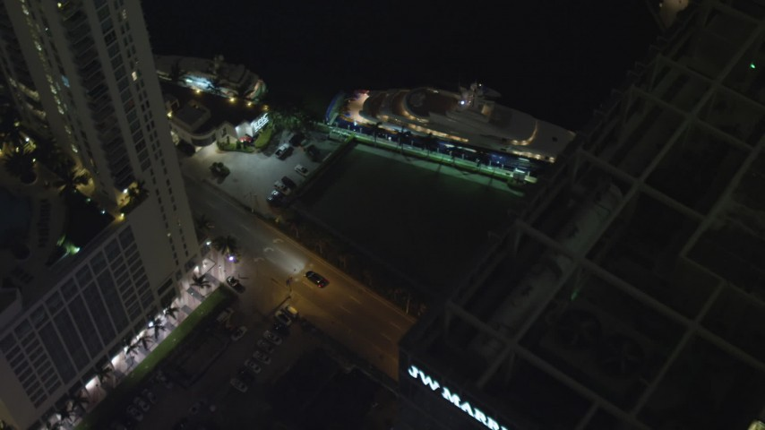 5K stock footage aerial video bird's eye fly over hotel to reveal yacht on river at night in Downtown Miami, Florida Aerial Stock Footage | AX0023_175