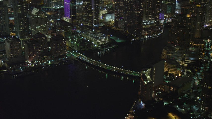 5K stock footage aerial video of Brickell Key Drive Bridge and waterfront skyscrapers at night in Downtown Miami, Florida Aerial Stock Footage | AX0023_179