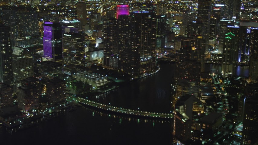 5K stock footage aerial video of Downtown Miami skyscrapers near Brickell Key Drive Bridge at night in Florida Aerial Stock Footage | AX0023_180