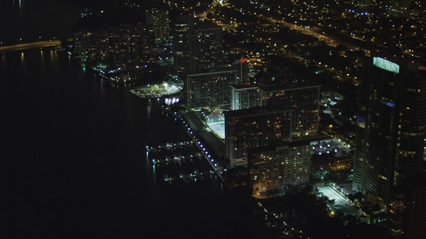 5K stock footage aerial video approach waterfront apartment buildings at night in Downtown Miami, Florida Aerial Stock Footage | AX0023_181