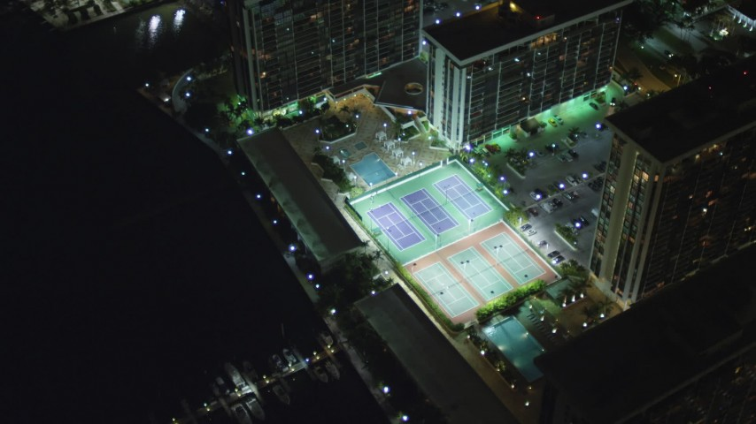 5K stock footage aerial video tilt while approaching waterfront apartment buildings at night in Downtown Miami, Florida Aerial Stock Footage | AX0023_182