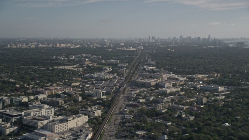 5K stock footage aerial video tilt from subway tracks, train, South Dixie Highway, reveal the skyline of Downtown Miami, Florida Aerial Stock Footage | AX0024_008