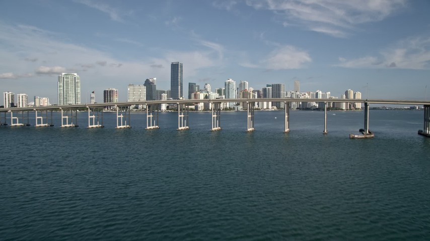 5K stock footage aerial video tilt from Biscayne Bay to reveal Rickenbacker Causeway, Downtown Miami, Florida Aerial Stock Footage | AX0024_052E