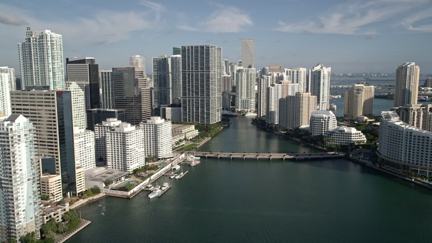 5K stock footage aerial video fly low over Biscayne Bay, reveal skyscrapers and Brickell Key, Downtown Miami, Florida Aerial Stock Footage | AX0024_054E