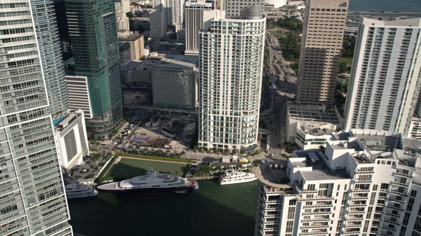 5K stock footage aerial video fly over Brickell Key Drive bridge, tilt to bird's eye of yachts on the Miami River, Downtown Miami, Florida Aerial Stock Footage | AX0024_056E