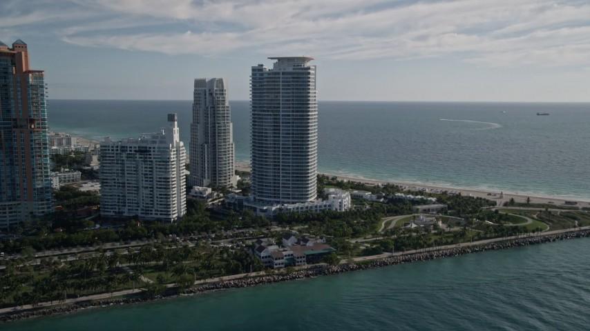 Flying by skyscrapers, Portofino Tower, South Beach, Miami Beach, Florida Aerial Stock Footage | AX0024_075