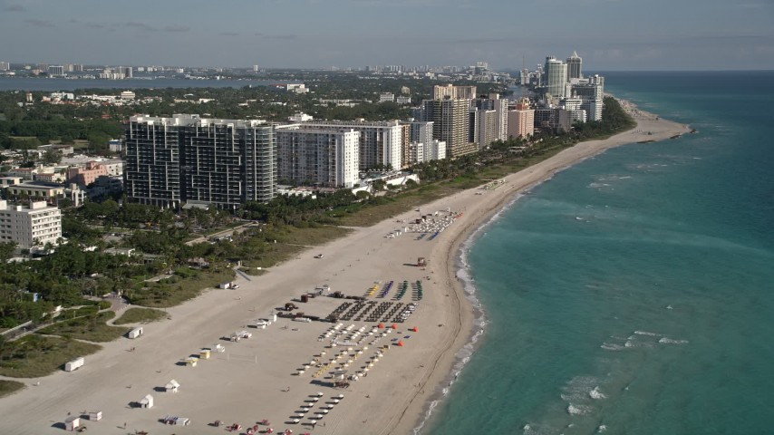 5K stock footage aerial video of flying over the beach and past South Beach hotels, Miami Beach, Florida Aerial Stock Footage | AX0024_080E