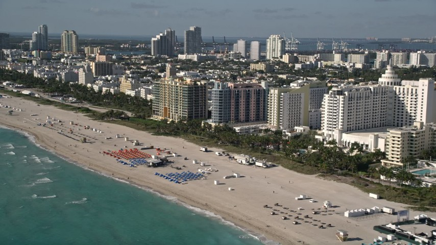 5K stock footage aerial video of flying along the shore of South Beach and passing hotels, Miami Beach, Florida Aerial Stock Footage | AX0024_093