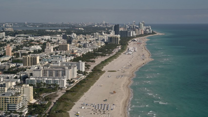5K stock footage aerial video of flying by South Beach coastline, reveal skyscrapers in Miami Beach, Florida Aerial Stock Footage | AX0024_113E