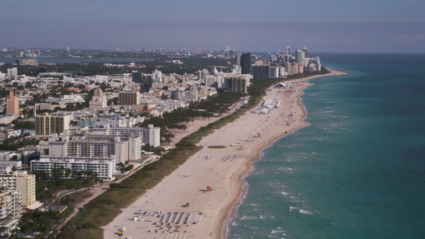 5K stock footage aerial video of flying inland from South Beach coastline, reveal skyscrapers, Miami Beach, Florida Aerial Stock Footage | AX0024_114