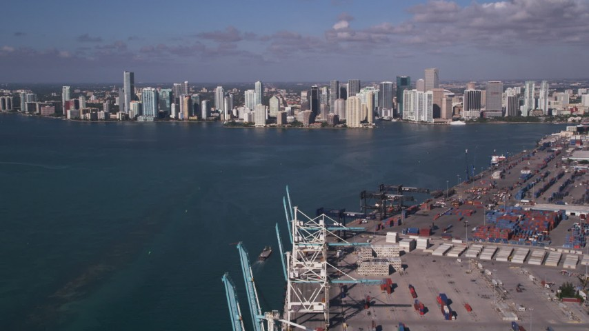 5K stock footage aerial video fly over cranes, cargo containers, Port of Miami, reveal Downtown Miami, Florida Aerial Stock Footage | AX0024_115