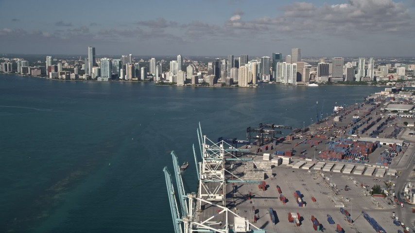 5K stock footage aerial video fly over cranes, cargo containers, Port of Miami, reveal Downtown Miami, Florida Aerial Stock Footage | AX0024_115E