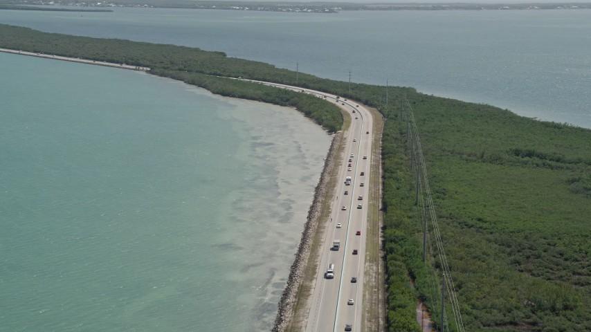 5K aerial stock footage video of traffic on Overseas Highway, reveal coastal mangroves, Key Largo, Florida Aerial Stock Footage | AX0025_048