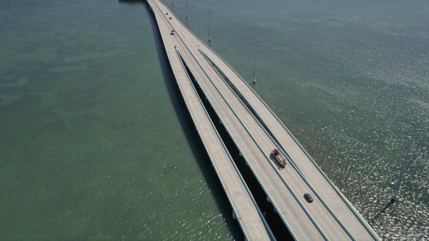 5K stock footage aerial video follow Overseas Highway bridge over Lake Surprise, reveal Key Largo, Florida Aerial Stock Footage | AX0025_054