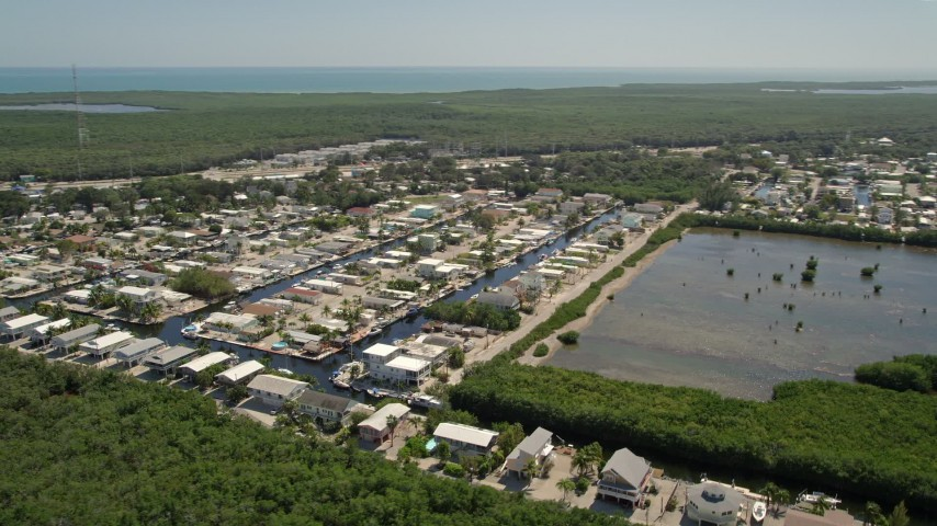 5K stock footage aerial video of flying by waterfront homes on canals, Key Largo, Florida Aerial Stock Footage | AX0025_056