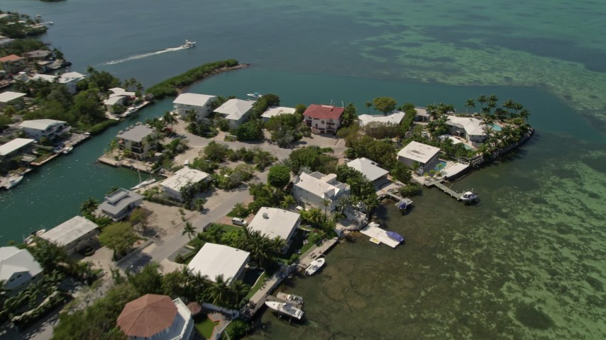 5K stock footage aerial video of panning across homes along the shore, tilt down, Tavernier, Florida Aerial Stock Footage | AX0025_092