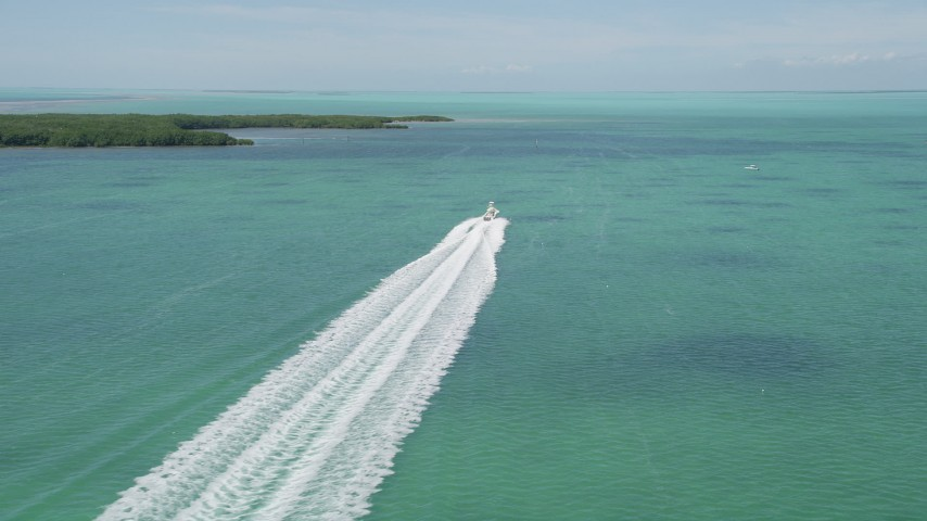 5K stock footage aerial video of following a fishing boat speeding past mangroves, Tavernier, Florida Aerial Stock Footage | AX0025_095