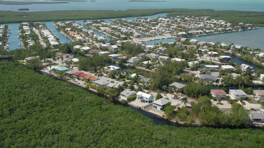 5K stock footage aerial video of approaching homes on canals along shore, Islamorada, Florida Aerial Stock Footage | AX0025_104