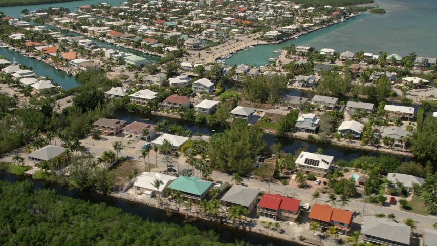5K stock footage aerial video of approaching homes on canals along shore, Islamorada, Florida Aerial Stock Footage | AX0025_104E