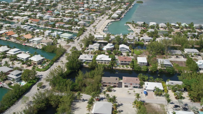 5K stock footage aerial video of flying by homes on canals along shore, Islamorada, Florida Aerial Stock Footage | AX0025_105