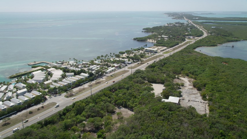 5K aerial video of following Overseas Highway, passing resorts and marinas, Islamorada, Florida Aerial Stock Footage | AX0025_106