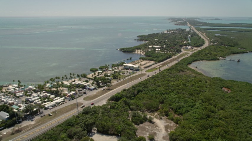 5K stock footage aerial video of following Overseas Highway, passing resorts and marinas, Islamorada, Florida Aerial Stock Footage | AX0025_106E