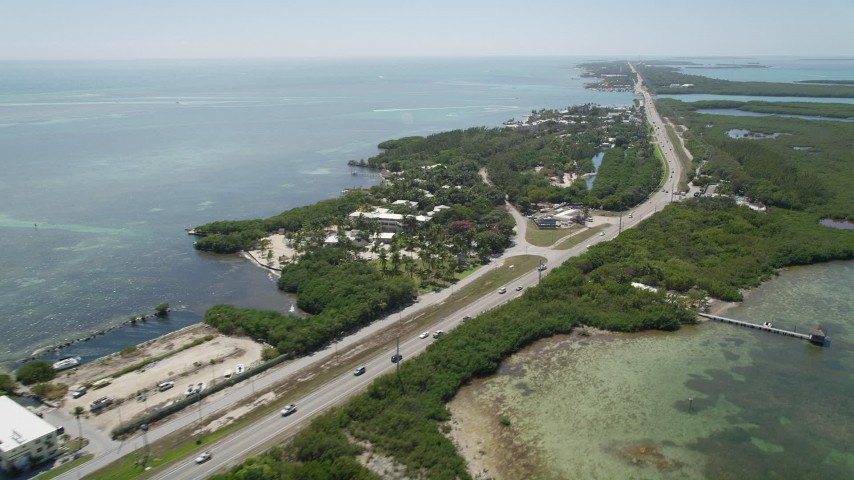 5K stock footage aerial video of the Overseas Highway while passing resorts and marinas, Islamorada, Florida Aerial Stock Footage | AX0025_107