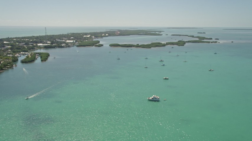 5K stock footage aerial video of flying over fishing boats and sailboats near the shore, Islamorada, Florida Aerial Stock Footage | AX0025_112