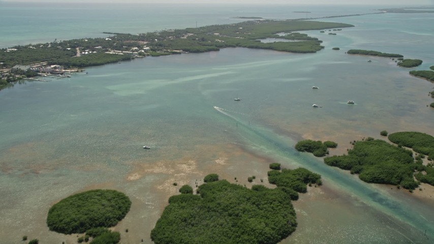 5K stock footage aerial video of flying over mangroves, approaching fishing boats off shore, Islamorada, Florida Aerial Stock Footage | AX0025_114