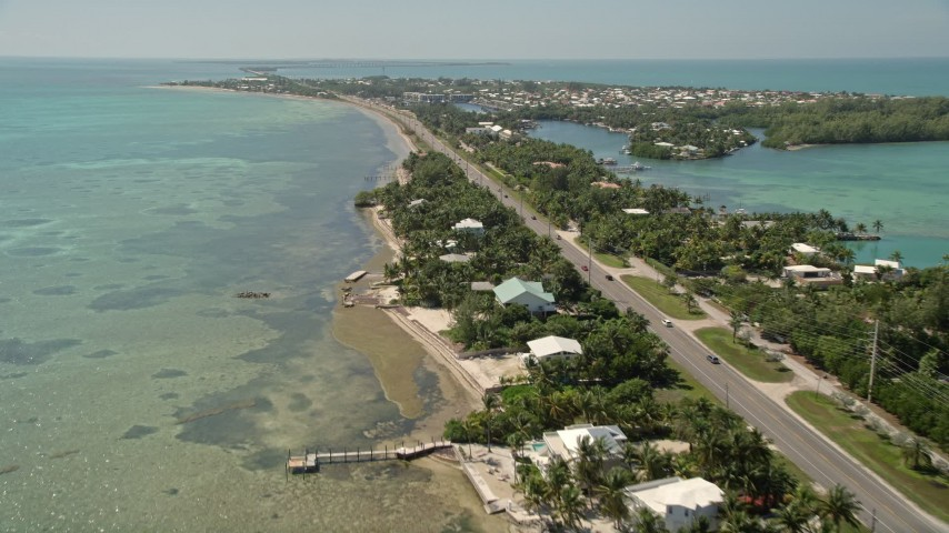 5K aerial video of flying by homes along the coast, Overseas Highway, Islamorada, Florida Aerial Stock Footage | AX0025_128