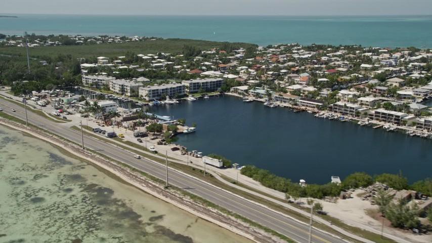 5K stock footage aerial video fly by Overseas Highway, neighborhoods, buildings on canals, Islamorada, Florida Aerial Stock Footage | AX0025_129