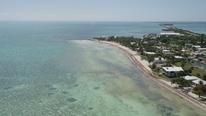 5K stock footage aerial video of flying by coastal homes, approaching end of beach, Islamorada, Florida Aerial Stock Footage | AX0025_130