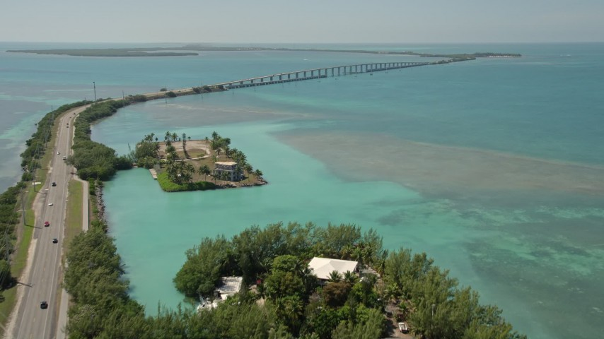 5K stock footage aerial video tilt from water to reveal Overseas Highway and Craig Key, Florida Aerial Stock Footage AX0025_133 | Axiom Images