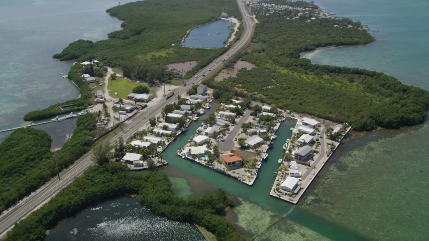 5K stock footage aerial video of approaching Grassy Key and tilt down to neighborhood, Marathon, Florida Aerial Stock Footage | AX0025_152