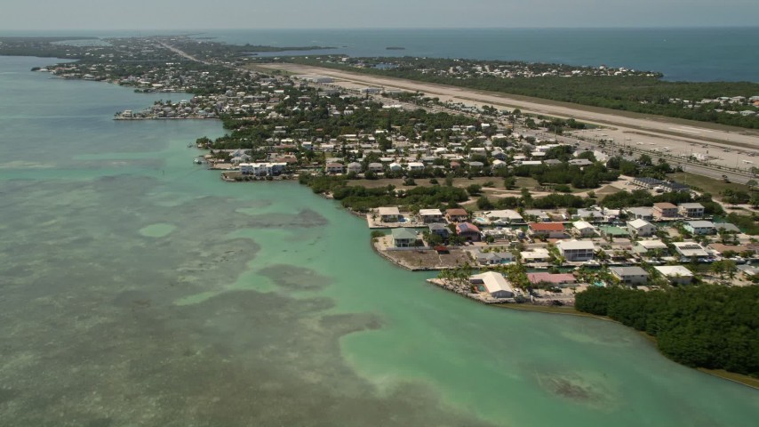 5K stock footage aerial video of flying by neighborhoods near Florida Keys Marathon Airport, Marathon, Florida Aerial Stock Footage | AX0025_165E
