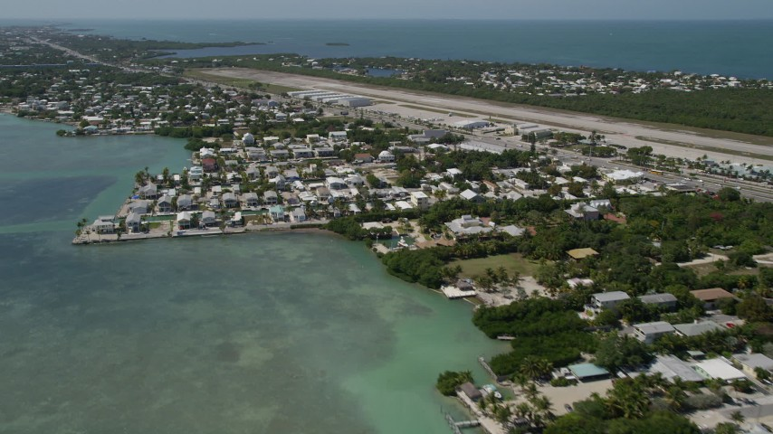 5K stock footage aerial video fly by coastal neighborhoods and Florida Keys Marathon Airport, Marathon, Florida Aerial Stock Footage | AX0025_166