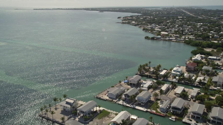 5K stock footage aerial video flying over the Atlantic Ocean near homes on the coast, Marathon, Florida Aerial Stock Footage | AX0026_004
