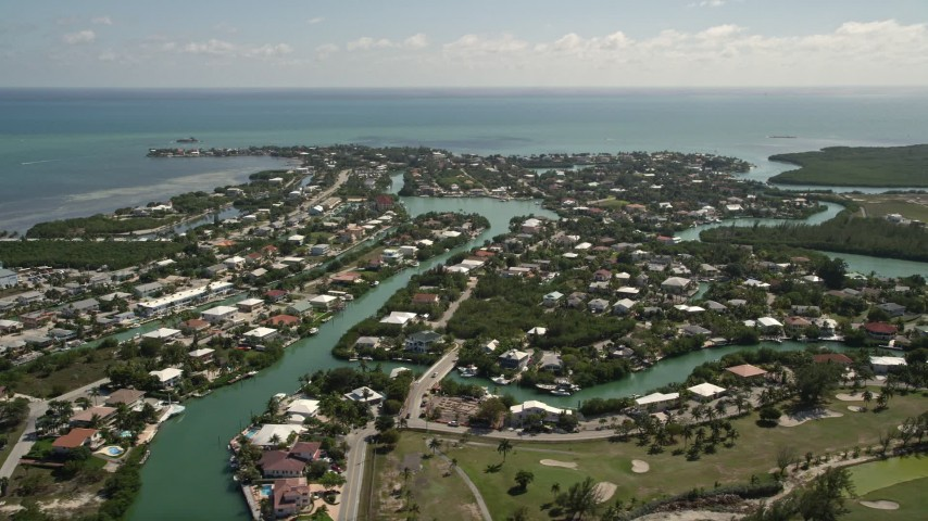 5K stock footage aerial video of flying by homes and canals along coast, Marathon, Florida Aerial Stock Footage | AX0026_009