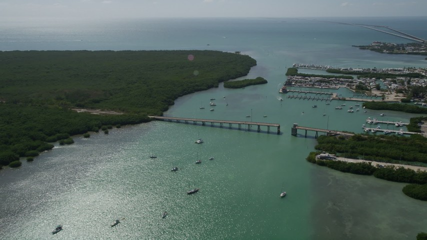 5K stock footage aerial video fly over sailboats and fishing boats, reveal incomplete bridge, Boot Key, Marathon, Florida Aerial Stock Footage | AX0026_011